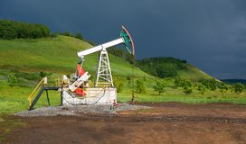 Pumping unit for pumping oil on a dark blue storm clouds Royalty Free Stock Photos