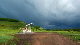 Pumping unit for pumping oil on a dark blue storm clouds Royalty Free Stock Image