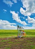 Pumping unit for pumping oil on a green meadow against a blue sky with clouds in summer Stock Image