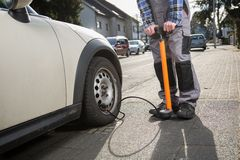 Pumping up a car tire after a malfunction Royalty Free Stock Photography