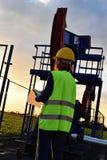 Pumpjack和石油工业工程师在黄昏时间 免版税库存照片
