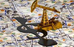 Pumpjack dourado e óleo derramado no dinheiro Fotos de Stock