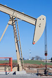 Pumpjack and Drilling Rig. Producing well site is 150 yards in front of a Drilling Rig Stock Photo