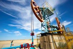 Pumpjack i Błękitnej flaga czerwony tło Pumpjack jest overground przejażdżką dla odwzajemnia tłokowej pompy w szybie naftowym fotografia royalty free