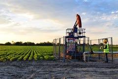 Pumpjack, Ingenieur und landwirtschaftliches Feld während der Dämmerungszeit Stockbild
