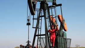 Pumpjack och oljefältarbetare. Royaltyfri Bild