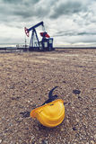 Pumpjack Oil Pump And Protective Helmet Royalty Free Stock Photos