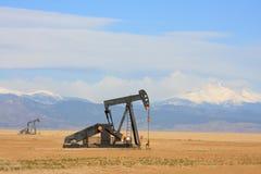 Pumpjack pumpendes Schmieröl, Schnee bedeckte Berge mit einer Kappe Lizenzfreie Stockfotografie