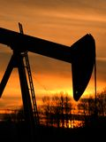 Pumpjack Sunset. A pumpjack silhouette against a colorful sky royalty free stock image
