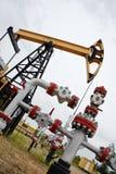 Pumpjack y pozo de petróleo. imagen de archivo libre de regalías