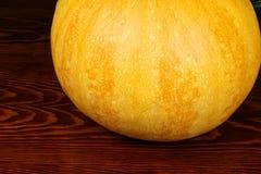 Pumpkin. Round orange pumpkin on dark wooden background Stock Photos