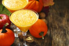 Pumpkin alcohol cocktail for fall and halloween parties. On wooden table, copy space Stock Image