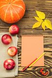 Pumpkin, apple and autumn leaves with a blank notebook on a wooden background. Royalty Free Stock Images
