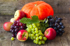 Pumpkin, apples, grapes on a wooden background Royalty Free Stock Photos