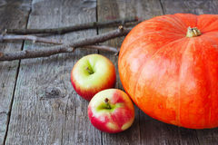 Pumpkin and apples on a wooden background Stock Image