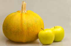 Pumpkin and apples. Yellow pumpkin and apples on a white background Royalty Free Stock Image