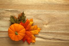 Pumpkin and autumn leaves. On wooden background Royalty Free Stock Images