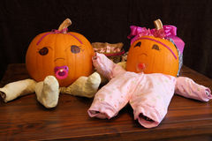 Pumpkin Babies in Onesies Wide Angle. Two pumpkins dressed up as princess babies with pacifiers Stock Photo