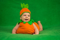 Pumpkin baby. 6-months baby in pumpkin costume sitting on green blanket Royalty Free Stock Images