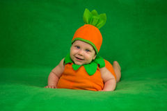 Pumpkin baby. 6-months baby in pumpkin costume sitting on green blanket Royalty Free Stock Photography