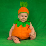 Pumpkin baby. 6-months baby in pumpkin costume sitting on green blanket Royalty Free Stock Image