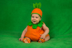 Pumpkin baby. 6-months baby in pumpkin costume sitting on green blanket Stock Image