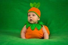Pumpkin baby. 6-months baby in pumpkin costume sitting on green blanket Stock Photos