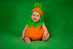 Pumpkin baby. 6-months baby in pumpkin costume sitting on green blanket Royalty Free Stock Photos