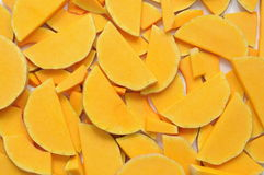 Pumpkin backgound. Slices of calabash pumpkin cut and randomly distributed to form an orange background Royalty Free Stock Image