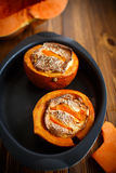Pumpkin baked with cheese and sesame seeds. On a baking sheet royalty free stock photo