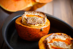 Pumpkin baked with cheese and sesame seeds. On a baking sheet royalty free stock image