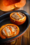 Pumpkin baked with cheese and sesame seeds. On a baking sheet stock images