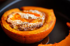 Pumpkin baked with cheese and sesame seeds. On a baking sheet royalty free stock images