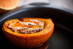 Pumpkin baked with cheese and sesame seeds. On a baking sheet royalty free stock photos