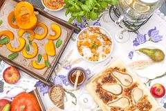 Pumpkin baked in the oven and a pie with a pear. Delicious autumn lunch. Top view. Copy space. stock photo
