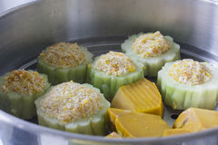 Pumpkin and bitter melon stuffed with vermicelli, tofu, corn and carrot while steaming in steaming pot Royalty Free Stock Photos