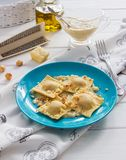 Ravioli blue plate cotton tablecloth hazelnut cheese. Pumpkin blue cheese italian ravioli wine cream sage sauce Royalty Free Stock Image
