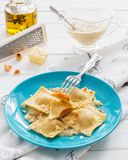 Ravioli blue plate cotton tablecloth hazelnut cheese. Pumpkin blue cheese italian ravioli wine cream sage sauce Stock Photos