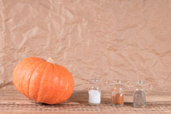 Pumpkin and bottle with spices Stock Photography