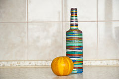 A pumpkin and a bottle on a table. Yellow pumpkin and multicolored bottle on a table royalty free stock image