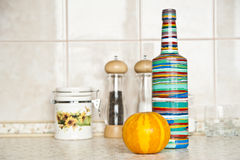 A pumpkin and a bottle on a table. Yellow pumpkin and multicolored bottle on a table stock photography