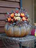 Pumpkin with a bouquet of flowers Stock Images