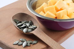 Pumpkin in a bowl and pumpkin kernels in a spoon Royalty Free Stock Photography