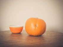 Pumpkin and bowl on table Royalty Free Stock Images