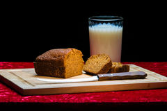 Pumpkin Bread and Milk. Pumpkin bread, knife and milk on wooden cutting board stock image