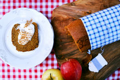 Pumpkin bread pound cake sliced with sour cream and cinnamon. With apples on checkered table cloth Royalty Free Stock Photography