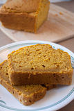 Pumpkin Bread. On a white plate with a loaf on a bamboo cutting board in back ground Stock Image