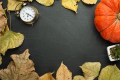 Pumpkin bright foliage alarm clock paper note pencil apple. autumn harvest style of the country. flat lying season food view from. Above dark background banner stock photography