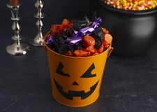 Pumpkin Bucket Filled with Various Wrapped Candies. On a Black Background royalty free stock photography