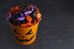 Pumpkin Bucket Filled with Various Wrapped Candies. On a White Background royalty free stock photos